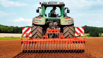 Traktor mit Arbeitsgerät auf dem Feld.