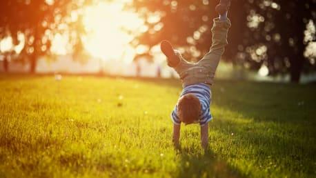 Junge macht Handstand im Garten