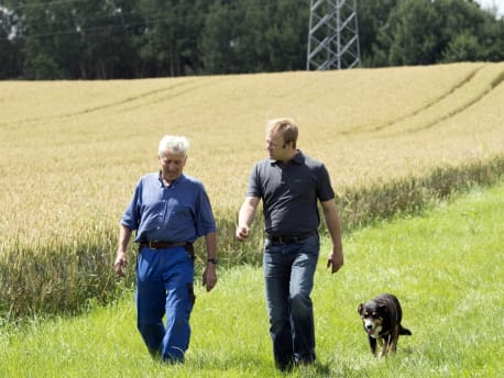 Lebensqualität. Zwei Männer mit Hund.