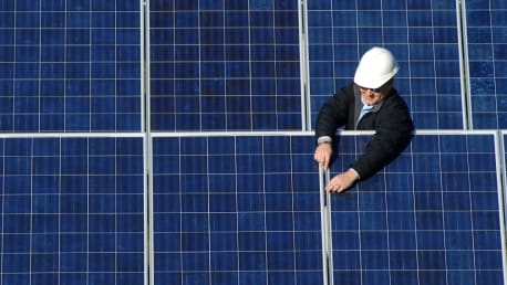 Picture shows a man in front of photovoltaic systems