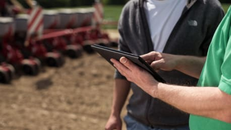 The picture shows two persons with tablet on a field