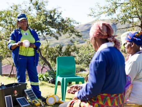Eine Frau zeigt eine durch Solarstrom angetriebene Glühbirne