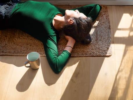 Frau liegt entspannt auf dem Boden