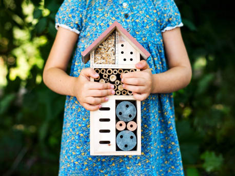 Child holding insect hotel