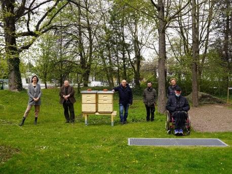Das Bild zeigt die Bienenstöcke mit dem BayWa Team und der Pfennigparade