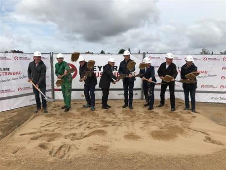 acht Personen mit Schaufel in der Hand auf der Baustelle im Sand stehend