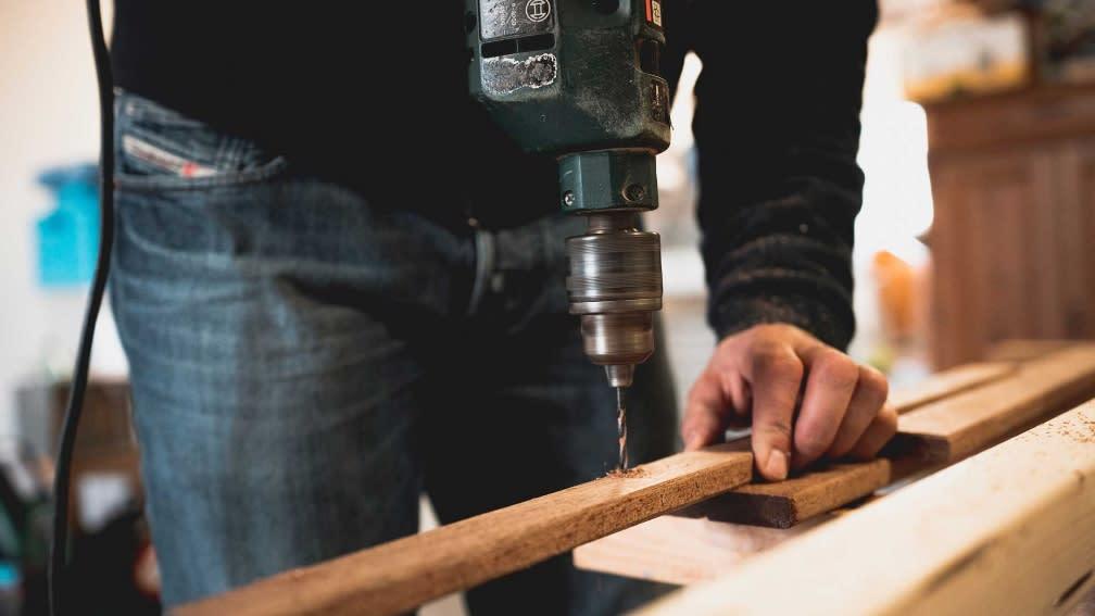 Mann, der ein Loch in ein Holzstück bohrt