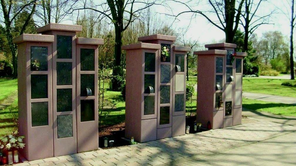 Urnenstelen System 3725, 3- und 4-reihig. Beton eingefärbt, Verschlussplatten New Impala und Jura Marmor.