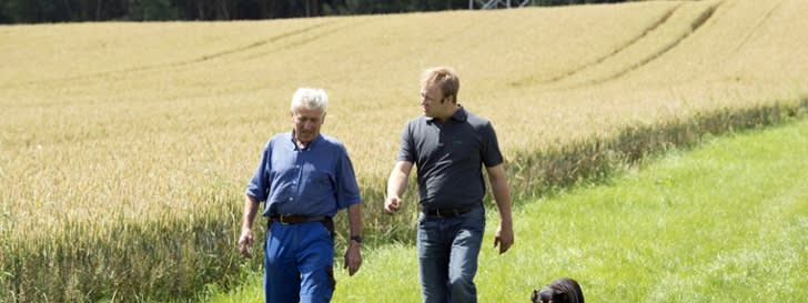 Two men with dog  walking on a field