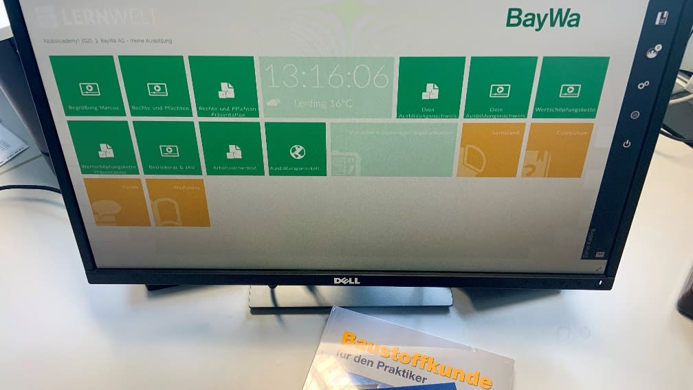 Computer-Bildschirm mit Anzeige der BayWa Baustoffe Lernwelt und zwei Büchern.