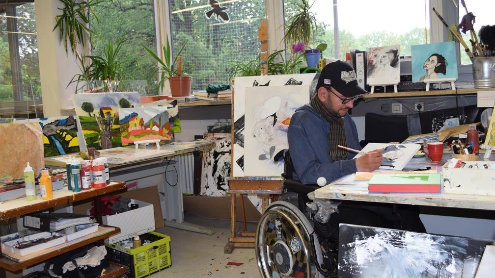 Person im Rollstuhl im Atelier beim malen