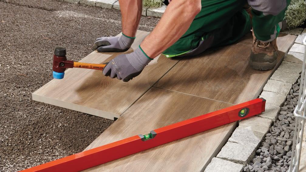 Bauarbeiter verlegt Casafino Terrassenplatten.