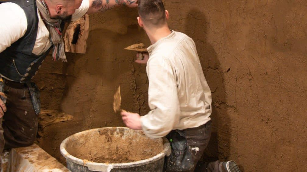 Lehmbauer Silvio Stolpe und sein Mitarbeiter verputzen eine Wand mit Lehm.