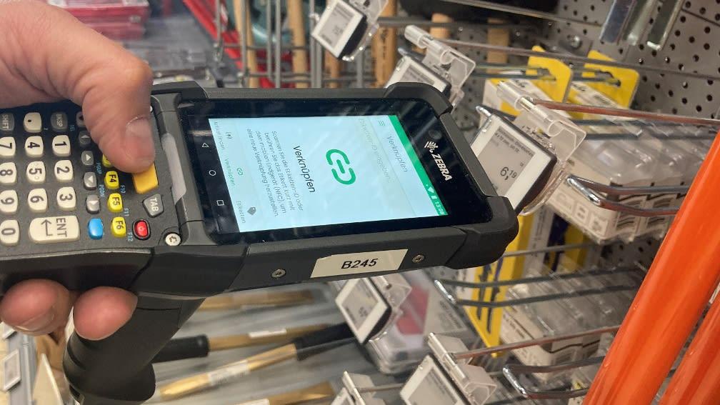 Ein Mitarbeiter ließt mit einem MDE-Gerät ein elektronisches Etikett aus.