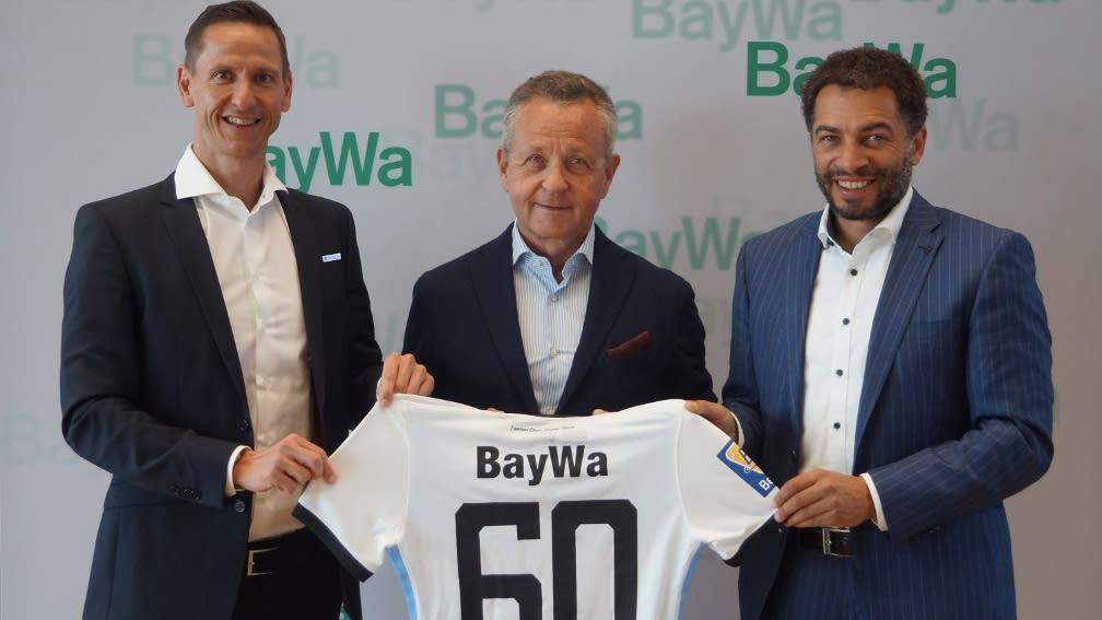 Drei Männer halten zusammen das Trikot des TSV 1860 München