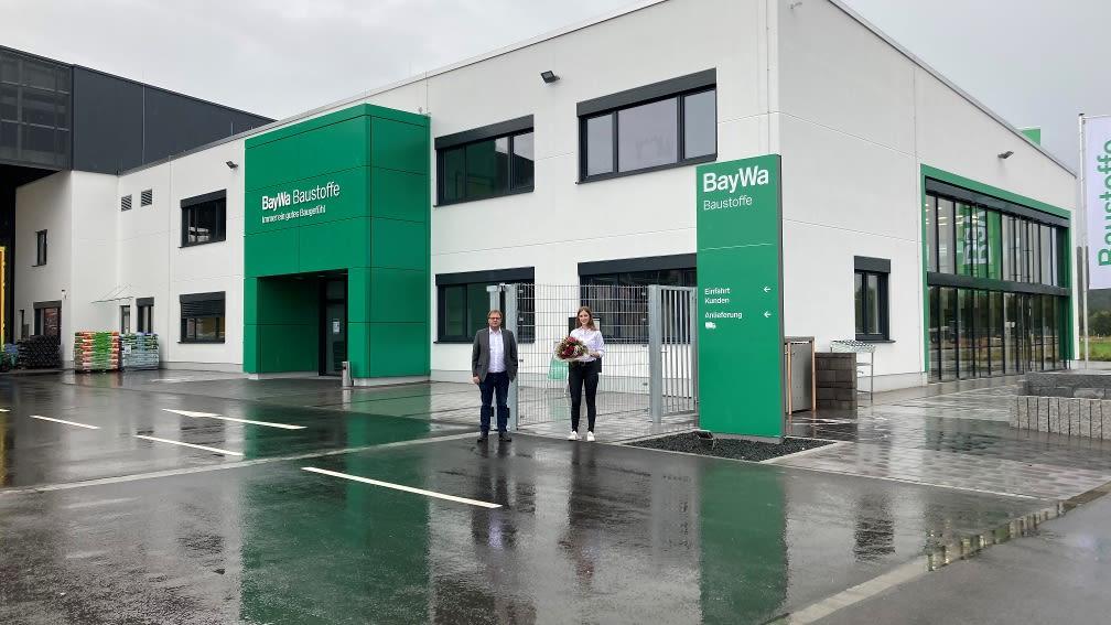 Frau und Mann vor Neubau des Baustoffbetriebs Wörth an der Donau.