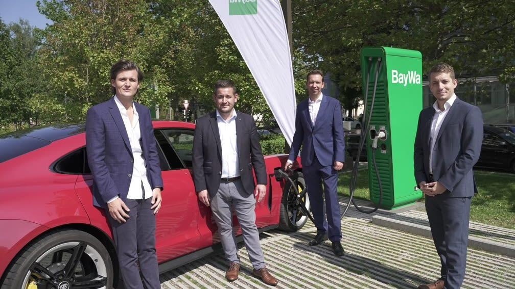 Vier Personen stehen vor rotem Auto