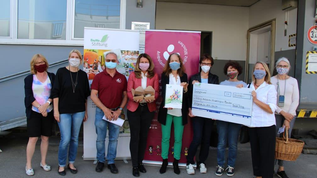 Maria Thon, Geschäftsführerin der BayWa Stiftung und Christine Bronner, Vorständin des AKM (Mitte) mit den ehrenamtlichen Fahrern.