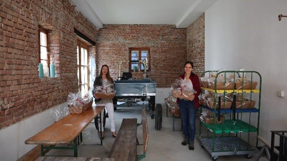 Zwei Personen präsentieren einen Geschenkkorb