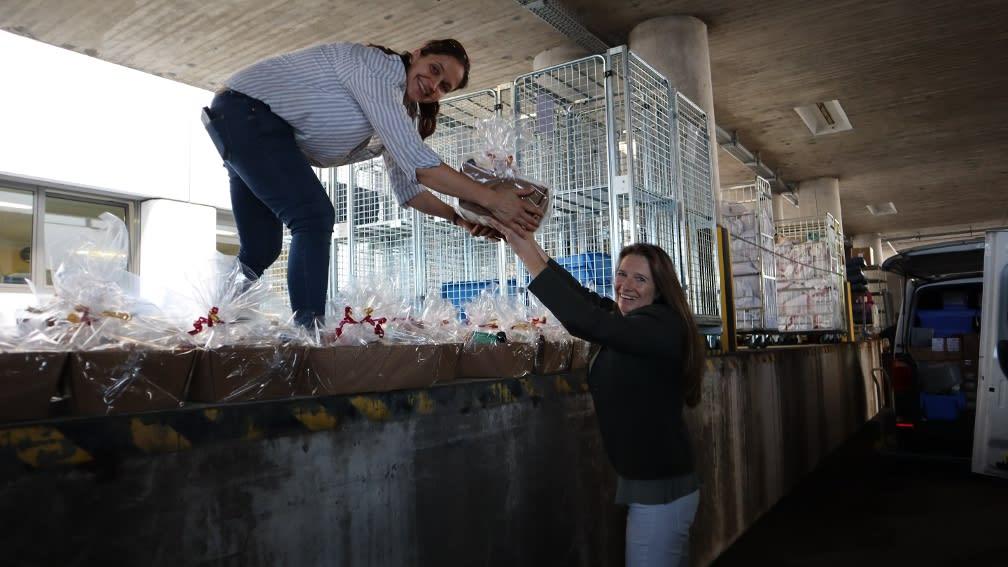 Zwei Personen übergeben einen Geschenkkorb