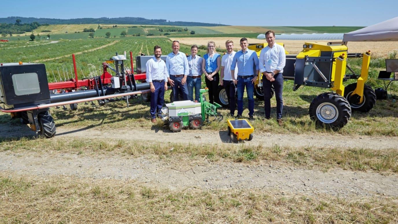 Seven people standing on an open field near four robots