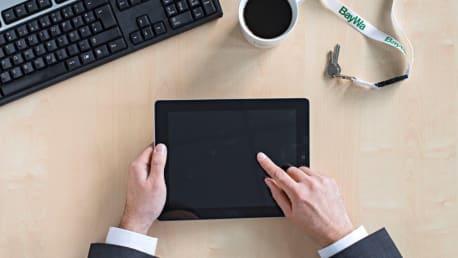 Schreibtisch mit den Händen einer Person, die gerade ein Tablet hält