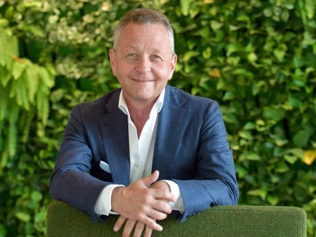 Picture shows Professor Lutz in front of a green-planted wall