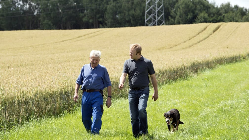 two men with a dog on a field