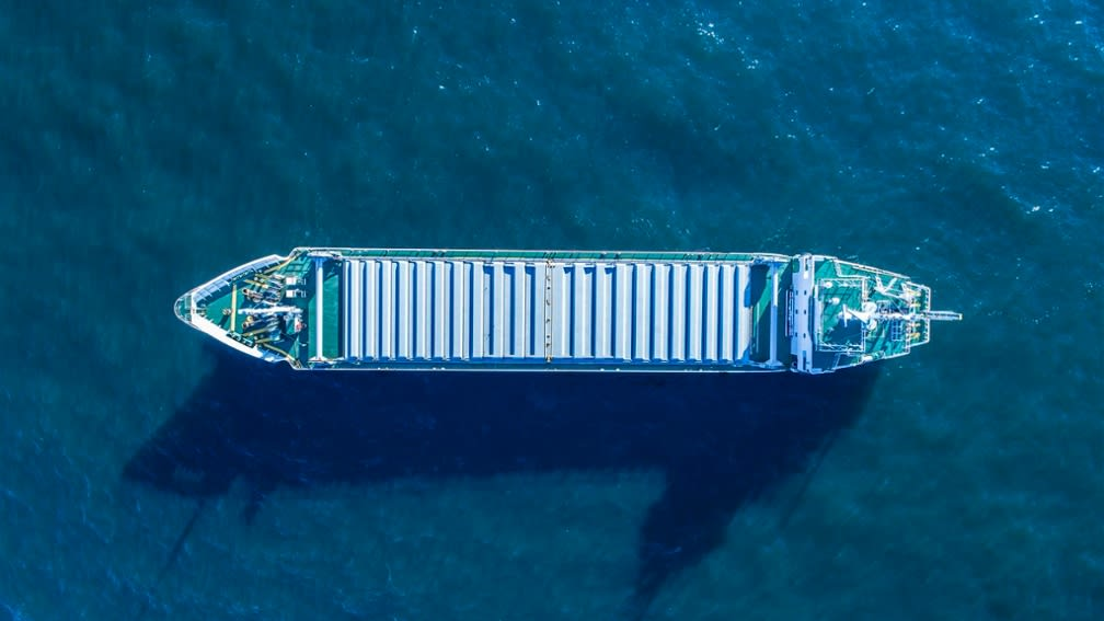Picture shows a container ship in the ocean from an aerial perspective