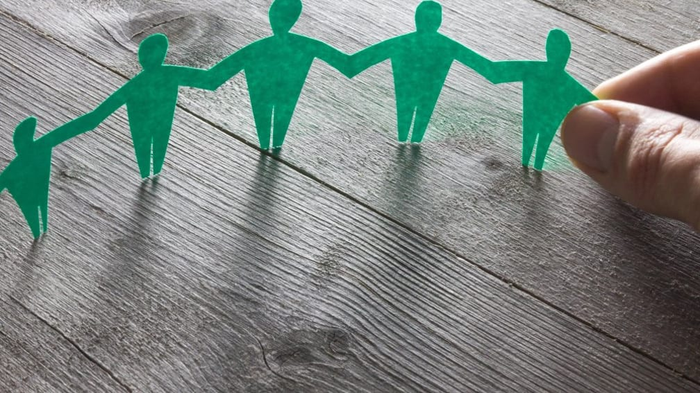 The picture shows 4 green paper figures