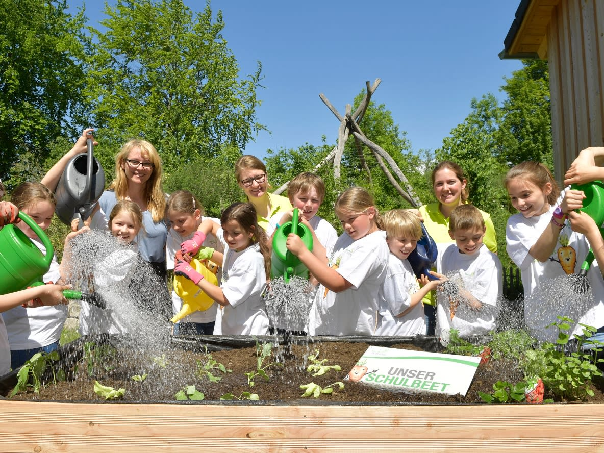 Picture shows a group of schoolchildren watering a bed