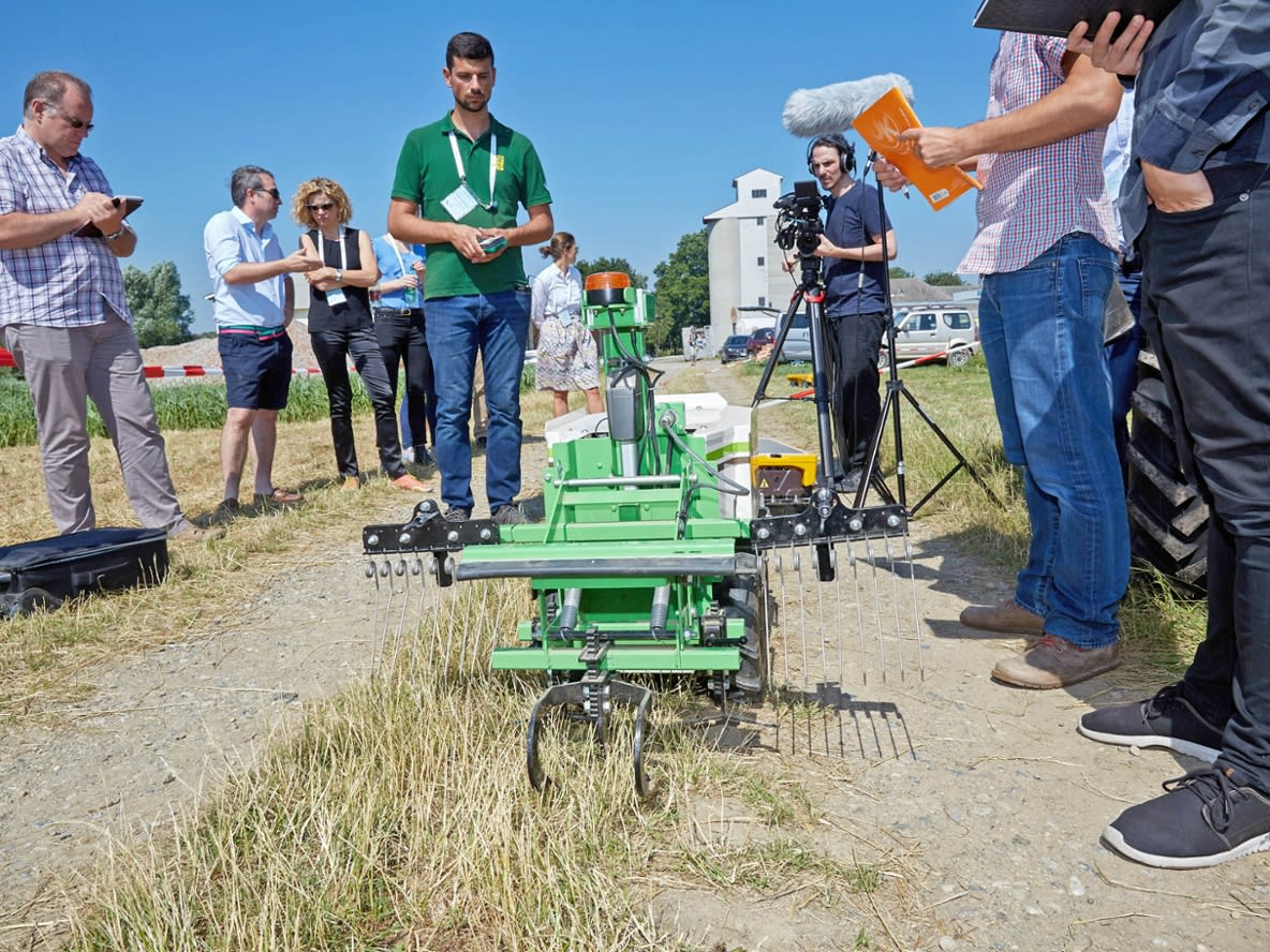 People in the field demonstrate the robot