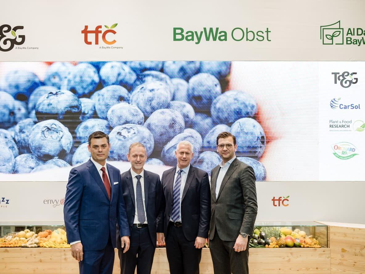 4 men in front of poster.