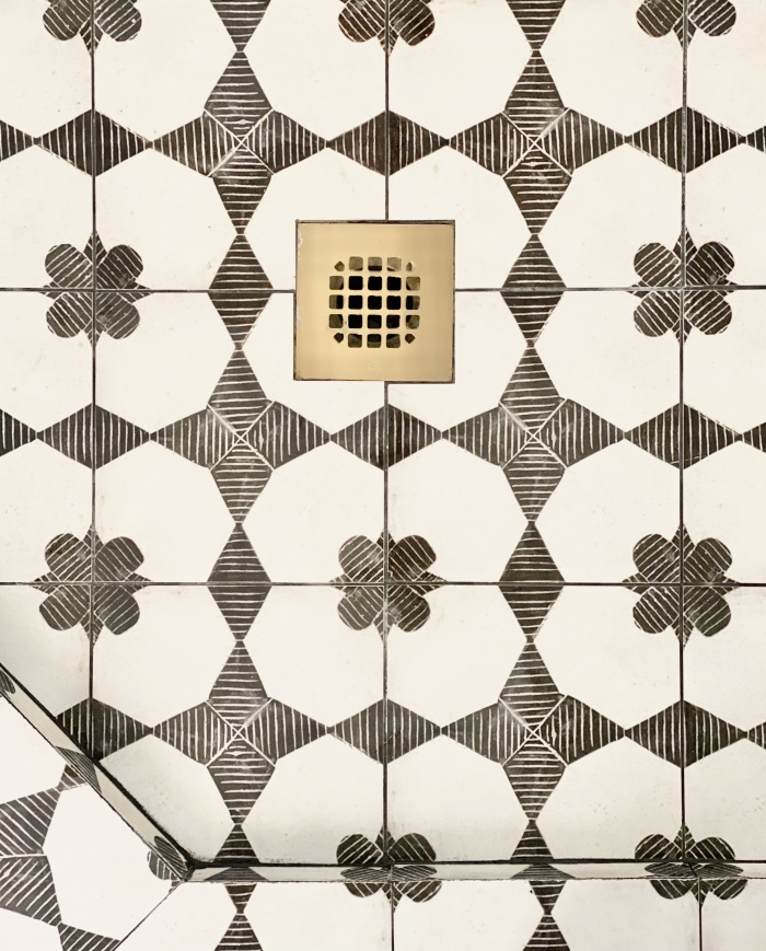 View of the shower drain tiled in Enchante 8x8 porcelain tile in Moderno