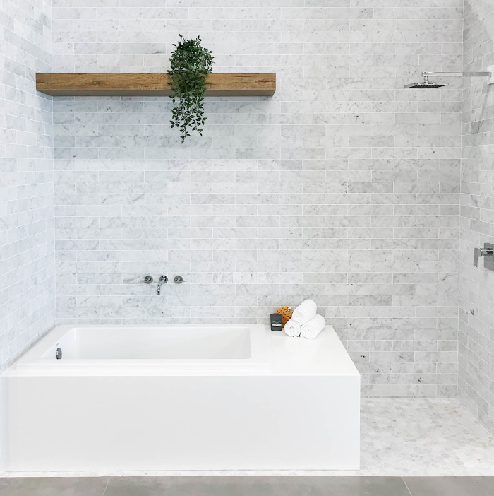"Tub Surround: Magnifica® Porcelain in Pure White | Walls: White Carrara 3x12 marble subway tile | Floor: White Carrara 2"" hexagon marble mosaic tile"