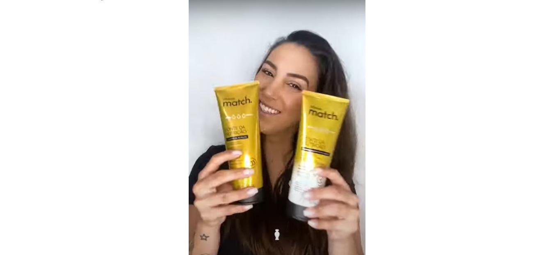 Mulher branca de cabelo preto sorrindo e segurando dois produtos na mão. A embalagem é amarela, é um shampoo e um condicionador.