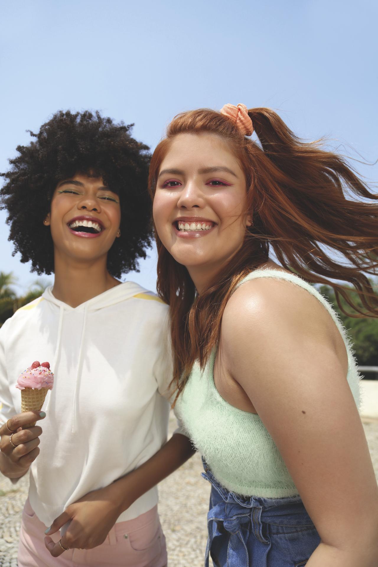 Imagem de duas meninas de frente e sorrindo. Eles estão em um ambiente aberto.