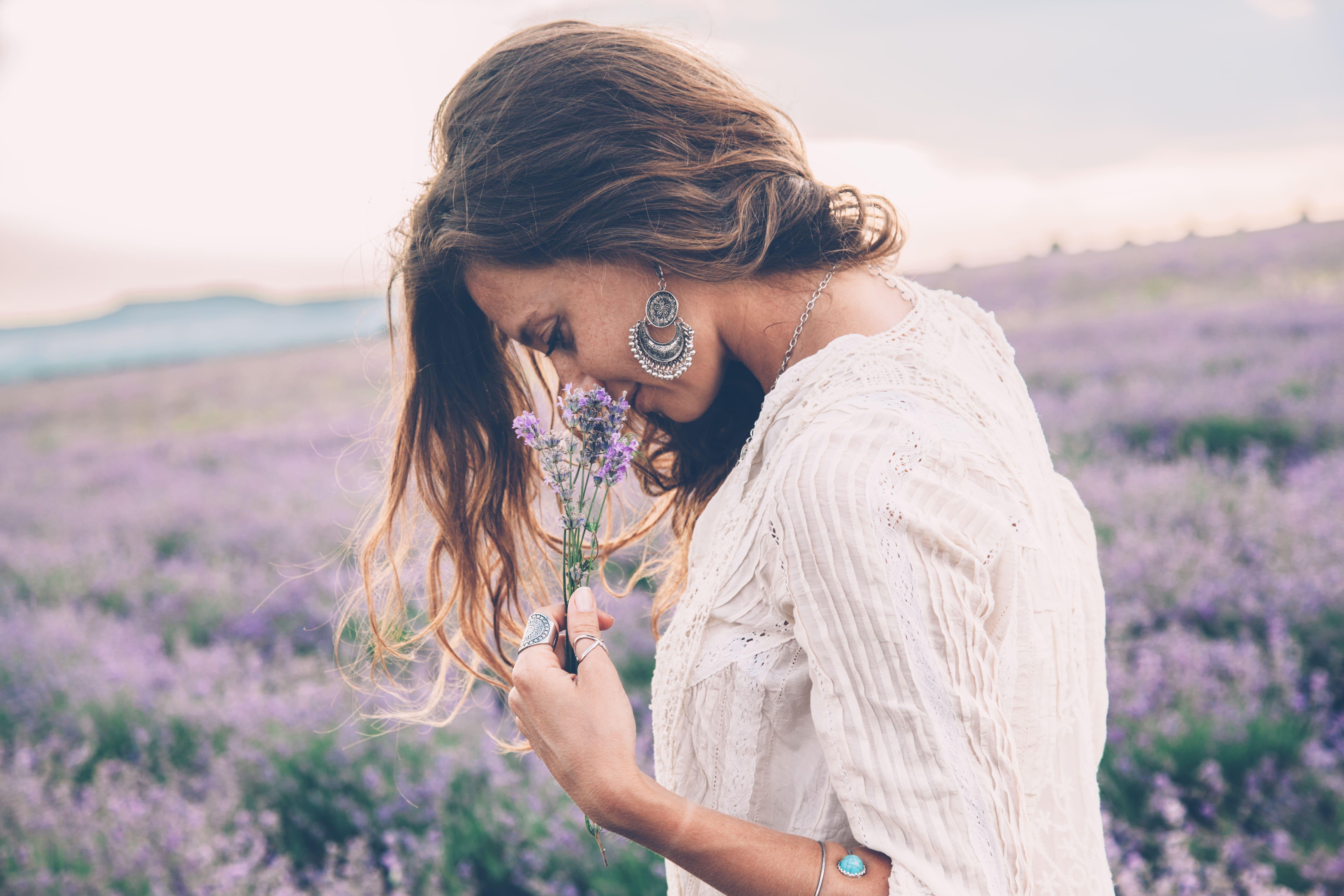 Mulher branca vestida de branco e com cabelos castanhos em um campo de Lavandas. Ela está cheirando flores de lavanda.