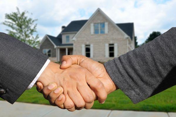 家を背景に握手をしている