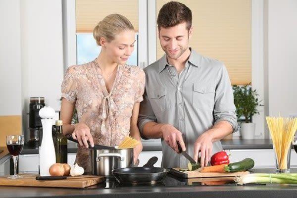 カップルが料理をしている画像