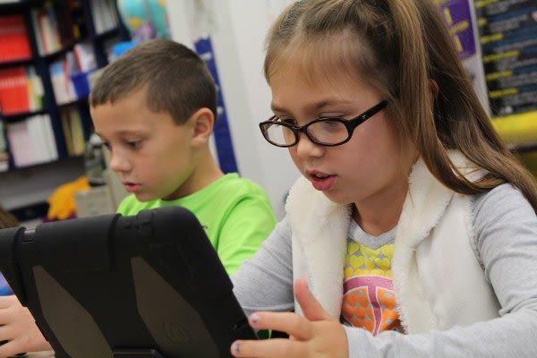少女がタブレットを見ている画像