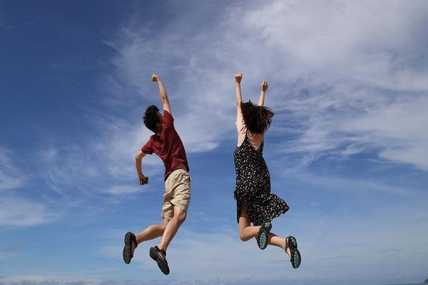 青空で男女がジャンプ