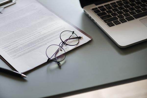 開いたノートパソコンと眼鏡