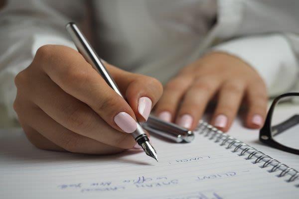 ノートに記入する女性の手元