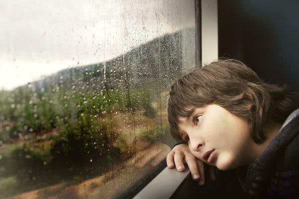 窓の外を眺める子供の画像