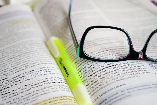 開いた本と黄色いマーカーとメガネ
