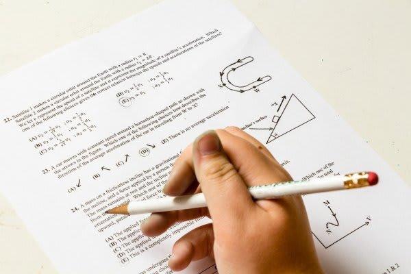 問題用紙と鉛筆を持つ手元