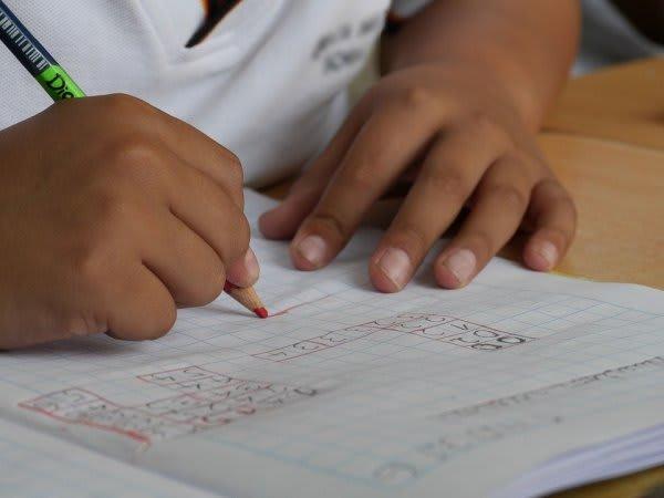 子どもが赤ペンで学習している画像