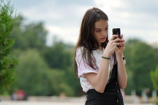 スマートフォンをもつ中学生