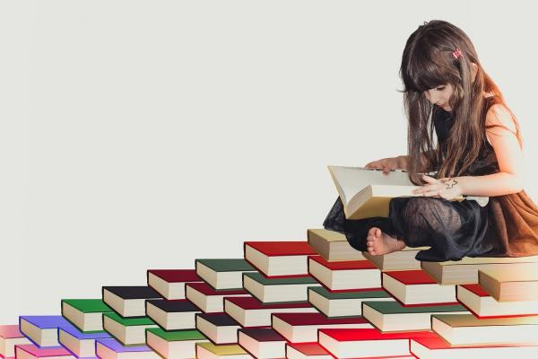 たくさんの本の上で読書する人